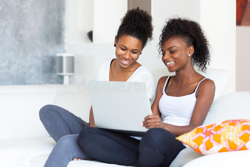 Muchachas afroamericanas del estudiante que usan un ordenador portátil - p negro fotos de archivo