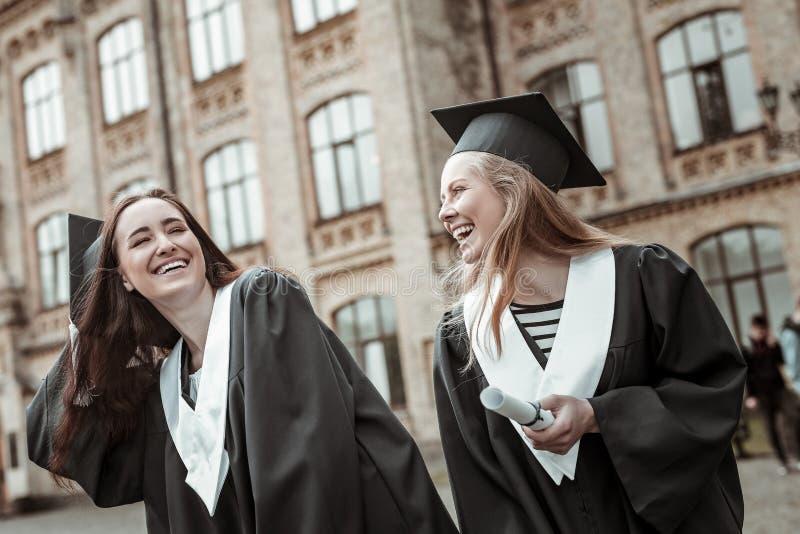 Muchachas alegres que se divierten mientras que se coloca cerca de universidad foto de archivo