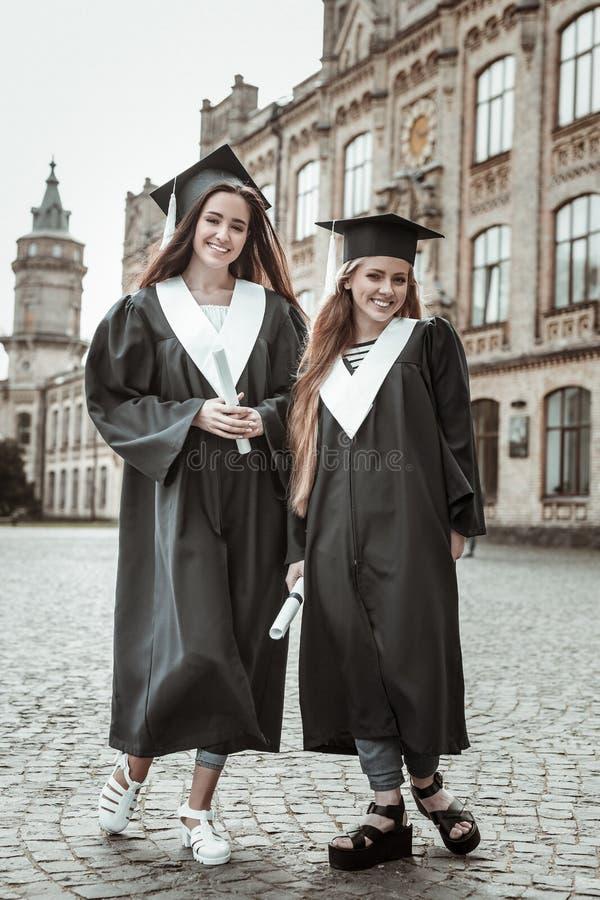 Muchachas alegres que tienen la fiesta de graduación en la universidad imagenes de archivo