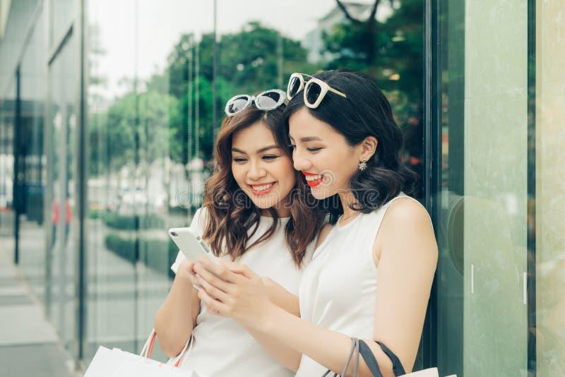 Muchachas asiáticas hermosas con los panieres usando smartphone en fotografía de archivo