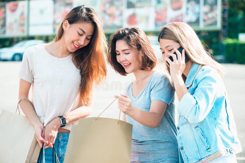 Muchachas asiáticas hermosas que sostienen los panieres, usando un teléfono elegante y sonriendo mientras que se coloca al aire l foto de archivo