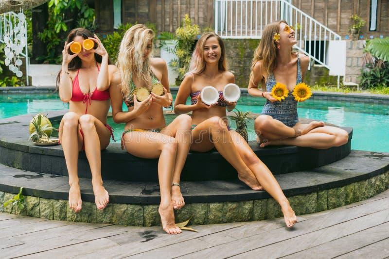 muchachas atractivas en bikinis que sonríen y que sostienen las frutas tropicales cortadas foto de archivo libre de regalías