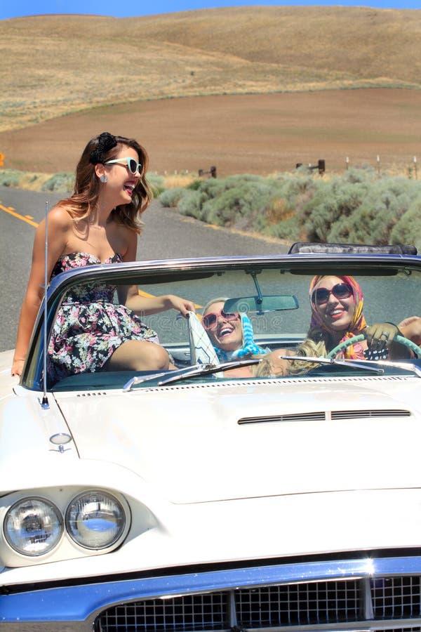 Muchachas atractivas felices en convertible imagenes de archivo