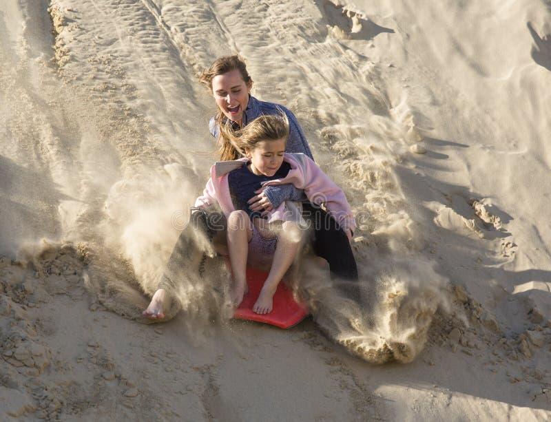 Muchachas aventureras que suben abajo de las dunas de arena imagen de archivo libre de regalías
