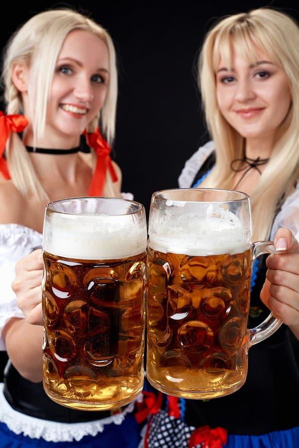 Muchachas bávaras jovenes y hermosas con dos tazas de cerveza en fondo negro fotos de archivo