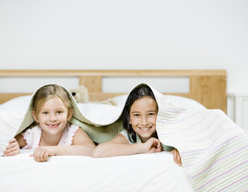 Muchachas bajo las hojas de cama foto de archivo libre de regalías