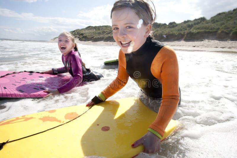 Muchachas Bodyboarding en el mar fotos de archivo libres de regalías