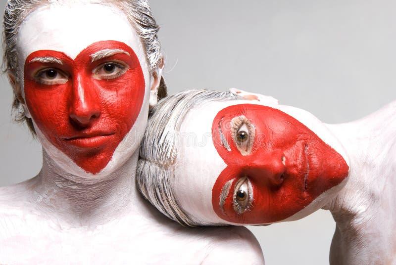 Muchachas bonitas con dimensiones de una variable rojas pintadas caras del corazón fotografía de archivo libre de regalías