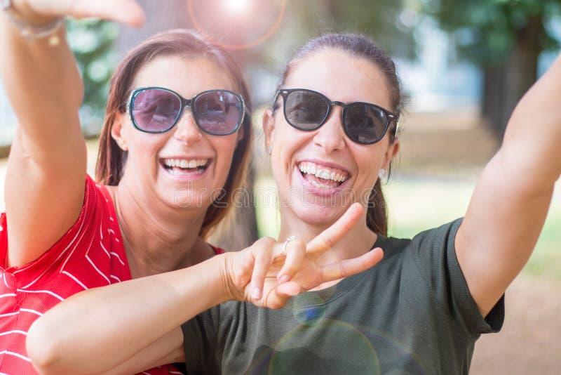 Muchachas caucásicas sonrientes que expresan emociones positivas a la cámara que hace la muestra de la victoria con sus manos fotos de archivo libres de regalías