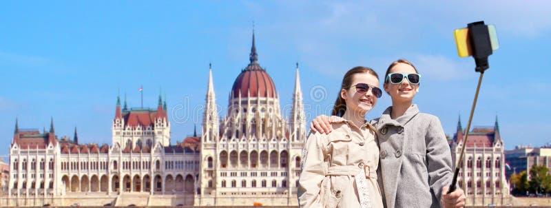 Muchachas con el palillo del selfie del smartphone en Budapest imagenes de archivo