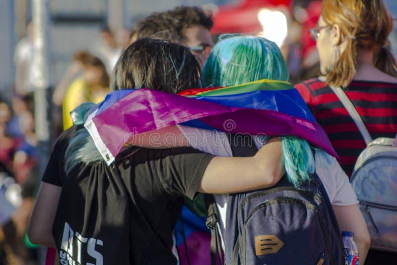Muchachas con la bandera del arco iris en un desfile de orgullo gay de LGBT fotos de archivo libres de regalías