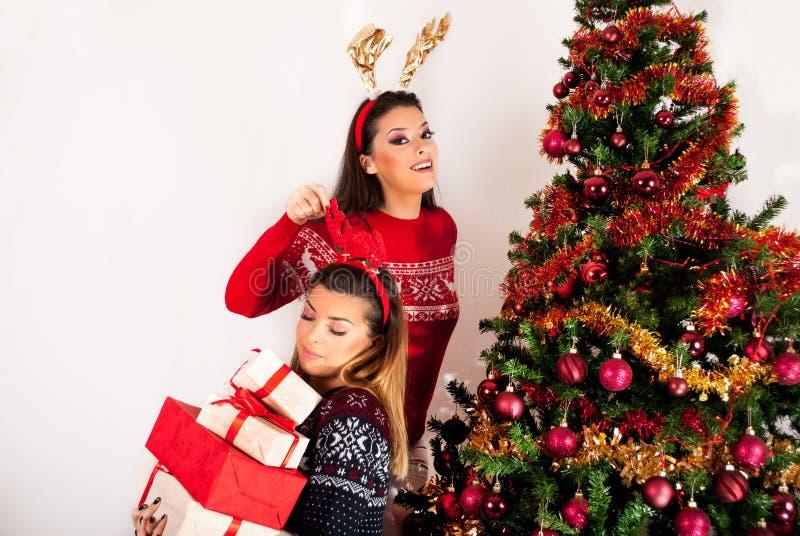 Muchachas con los cuernos del reno a mano y muchas cajas y árbol de navidad de regalo fotos de archivo