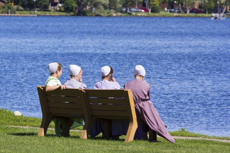 Muchachas de Amish que se sientan por el lago fotos de archivo libres de regalías