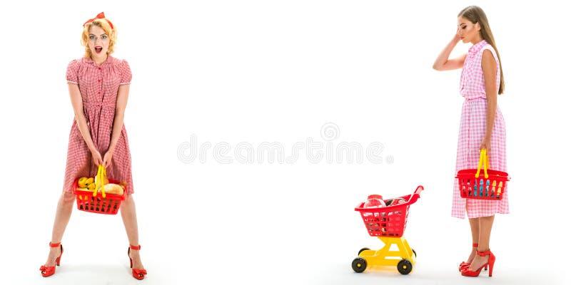 Muchachas de compras felices con el carro lleno mujeres del ama de casa del vintage que van a hacer el pago en supermercado ahorr imagen de archivo