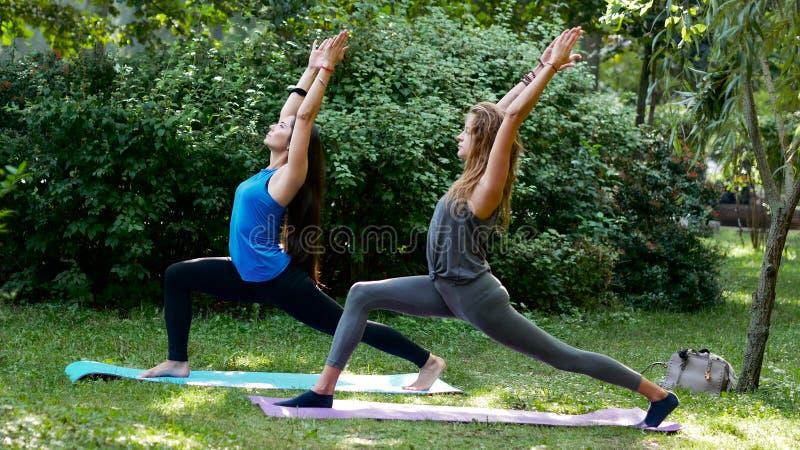 Muchachas de la aptitud que hacen la yoga al aire libre Virabhadrasana fotografía de archivo