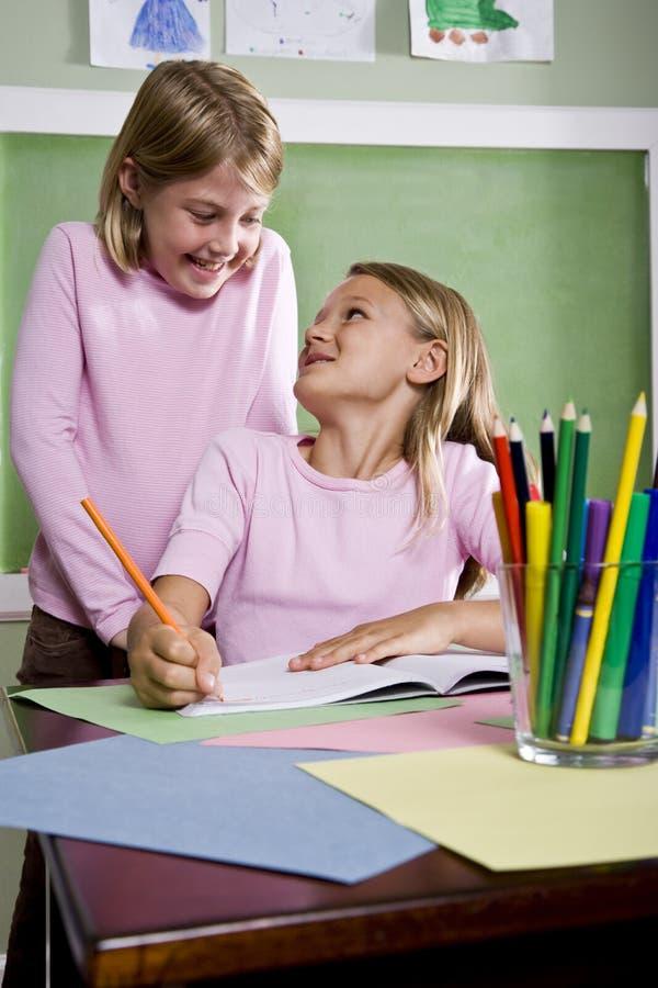 Muchachas de la escuela que escriben en cuaderno en sala de clase foto de archivo