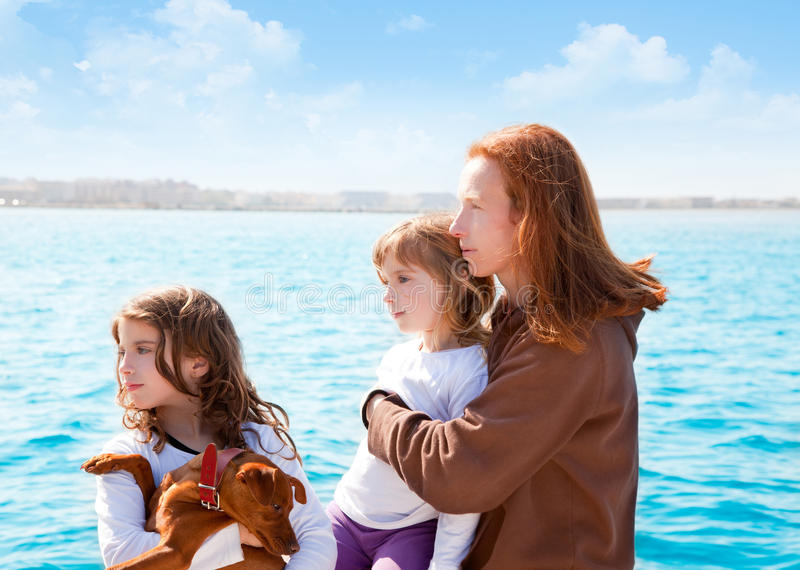 Muchachas de la familia con el perro en el mar imagenes de archivo