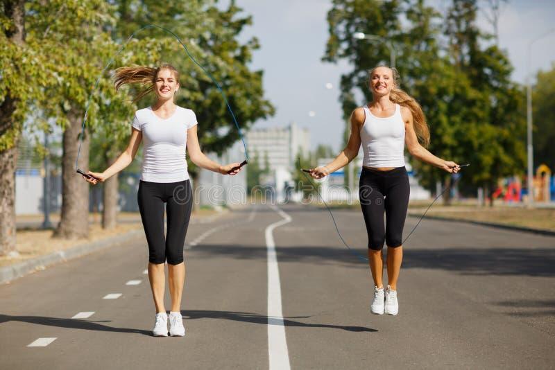 Muchachas de la gimnasia con las cuerdas de salto en un fondo del parque Se divierte a amigos Concepto activo de la juventud fotos de archivo