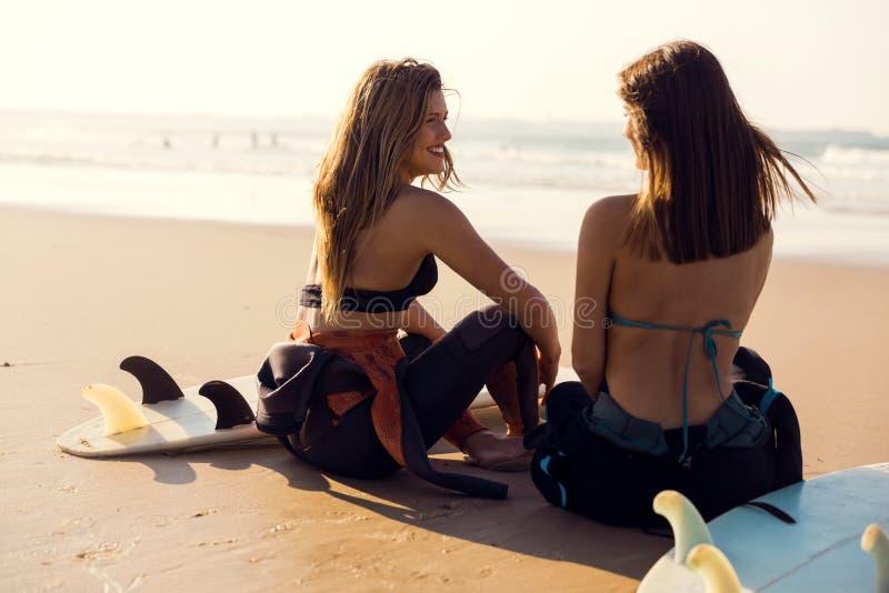 Muchachas de la persona que practica surf en la playa imagen de archivo