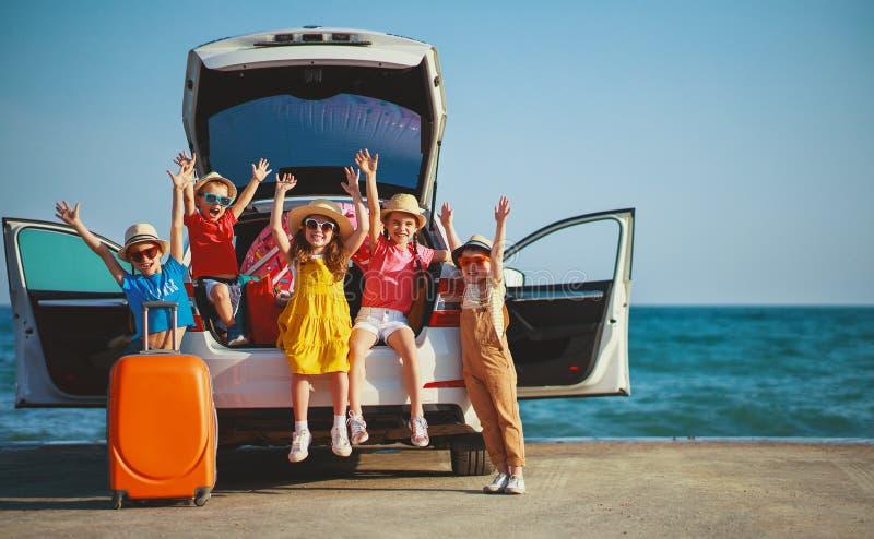 Muchachas de los niños del grupo y novios felices en paseo del coche al viaje del verano imagenes de archivo