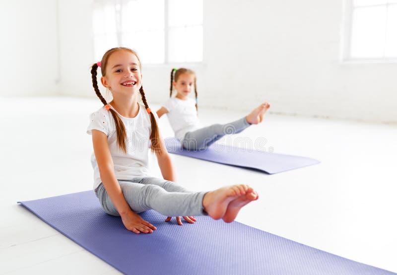 Muchachas de los niños que hacen yoga y la gimnasia en gimnasio foto de archivo
