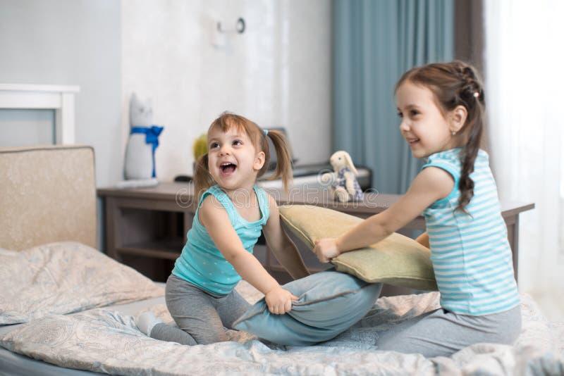 Muchachas de los niños que luchan usando las almohadas en dormitorio foto de archivo libre de regalías