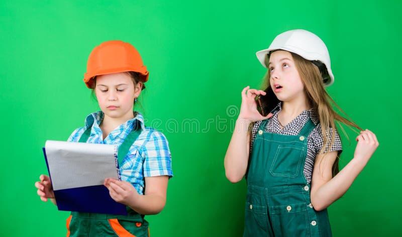 Muchachas de los ni?os que planean la renovaci?n Las muchachas preliminares de los ni?os proporcionan la renovaci?n su fondo verd fotos de archivo libres de regalías