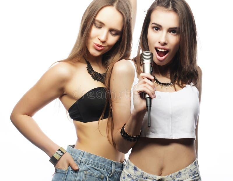 muchachas del inconformista de la belleza con un micrófono que cantan y que se divierten imagen de archivo
