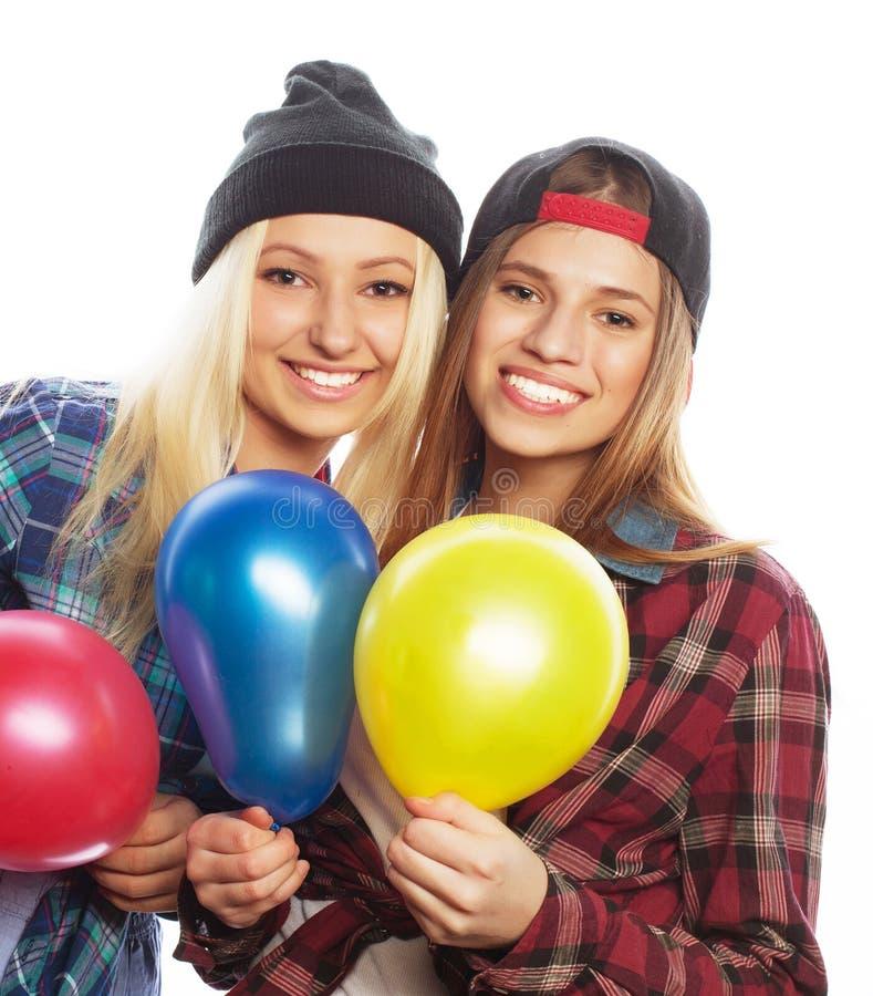 Muchachas del inconformista que sonríen y que sostienen los globos coloreados fotografía de archivo