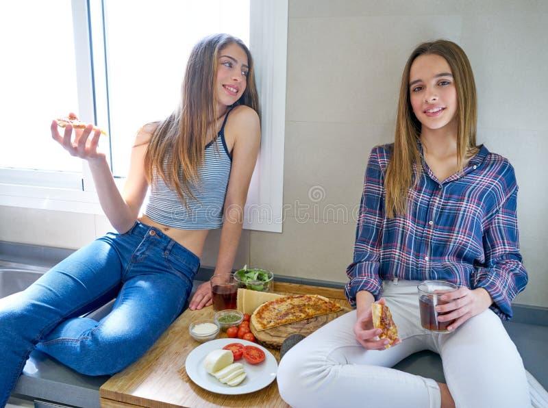 Muchachas del mejor amigo que comen la pizza en la cocina imagen de archivo libre de regalías