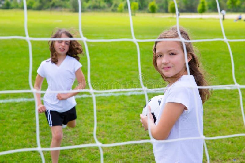Muchachas del niño del fútbol del fútbol que juegan en campo fotos de archivo