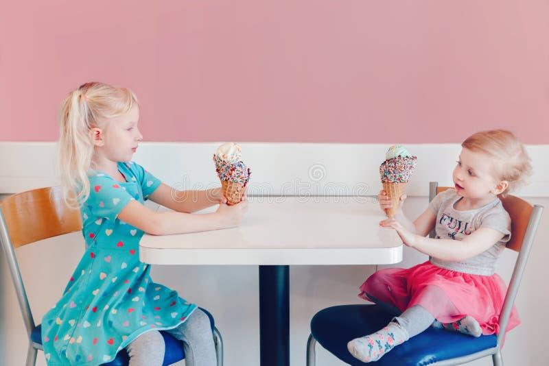 Muchachas divertidas de los ni?os que sientan junto la jactancia jact?ndose su helado imágenes de archivo libres de regalías