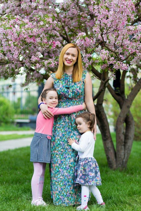 Muchachas divertidas que caminan en el césped con su madre Las hermanas juegan así como mamá Cuidado maternal Familia feliz fotografía de archivo libre de regalías