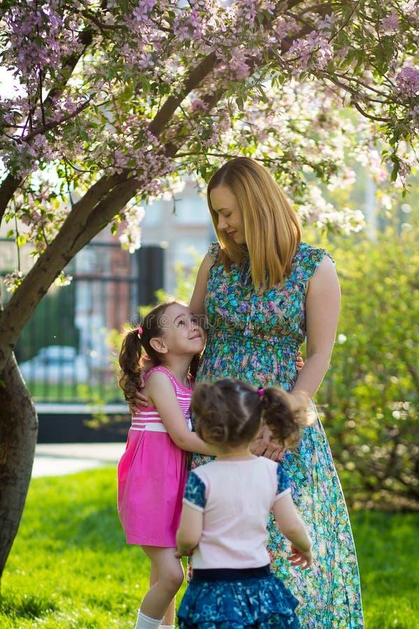 Muchachas divertidas que caminan en el c?sped con su madre Las hermanas juegan as? como mam? Cuidado maternal Familia feliz foto de archivo libre de regalías
