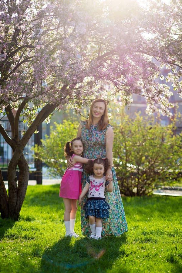Muchachas divertidas que caminan en el c?sped con su madre Las hermanas juegan as? como mam? Cuidado maternal Familia feliz imagen de archivo