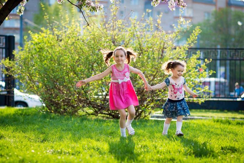 Muchachas divertidas que caminan en el c?sped con su madre Las hermanas juegan as? como mam? Cuidado maternal Familia feliz fotografía de archivo libre de regalías