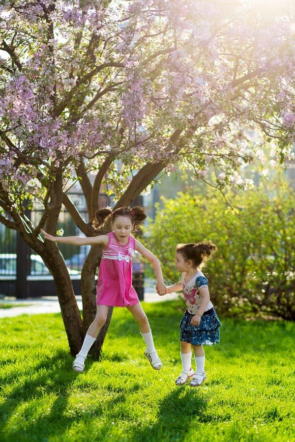 Muchachas divertidas que caminan en el c?sped con su madre Las hermanas juegan as? como mam? Cuidado maternal Familia feliz fotos de archivo libres de regalías
