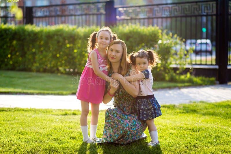 Muchachas divertidas que caminan en el c?sped con su madre Las hermanas juegan as? como mam? Cuidado maternal Familia feliz imagen de archivo libre de regalías