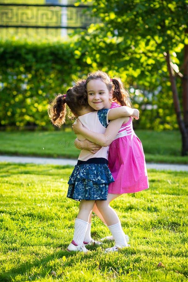 Muchachas divertidas que caminan en el c?sped con su madre Las hermanas juegan as? como mam? Cuidado maternal Familia feliz fotos de archivo