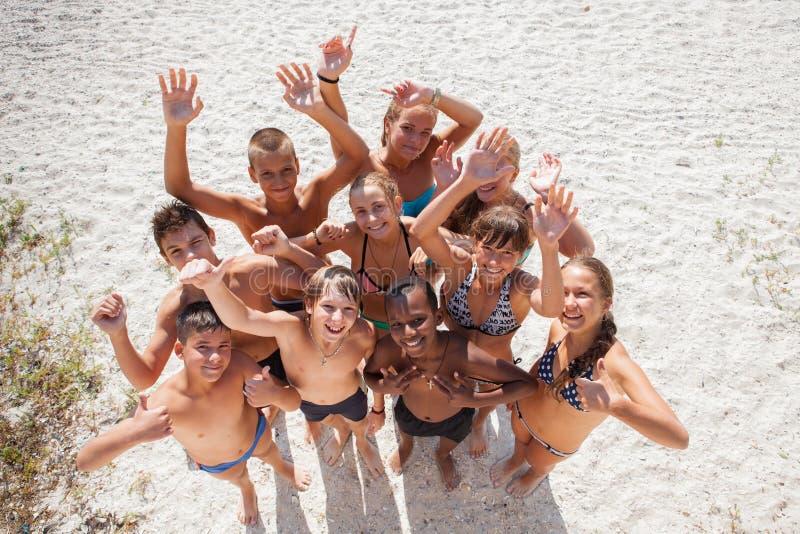 Muchachas e individuos en la arena el vacaciones de verano imagen de archivo libre de regalías