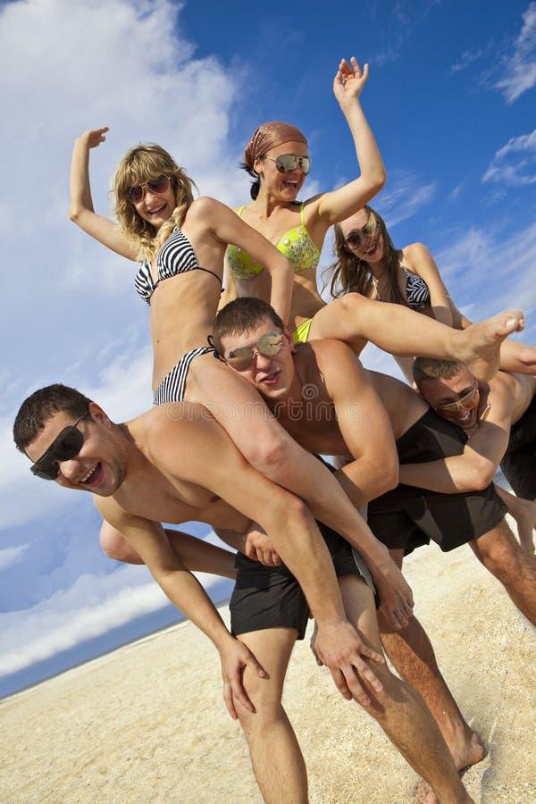 Muchachas e individuos en la playa imágenes de archivo libres de regalías