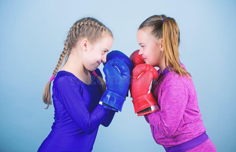 Muchachas en deporte del boxeo Ni?os del boxeador en guantes de boxeo Boxeadores lindos de las muchachas en fondo azul Amistad co fotos de archivo libres de regalías