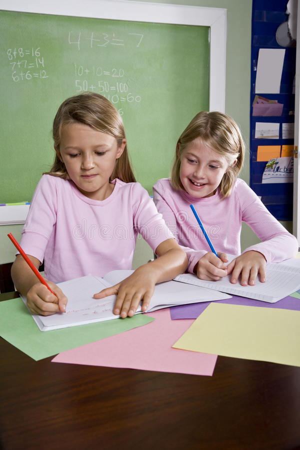 Muchachas en la sala de clase que hace el schoolwork, escribiendo imagen de archivo libre de regalías