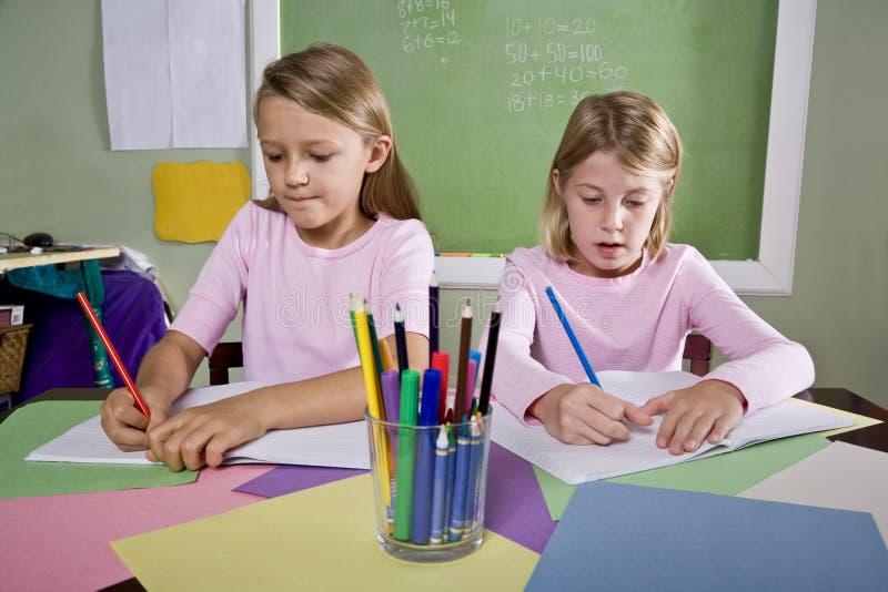 Muchachas en la sala de clase que hace el schoolwork, escribiendo imagenes de archivo