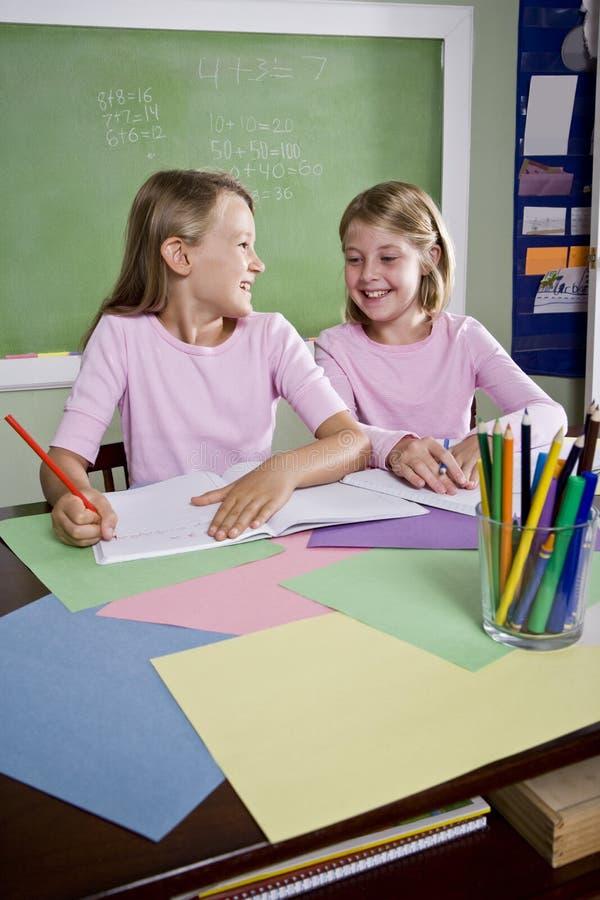 Muchachas en la sala de clase que hace el schoolwork, escribiendo fotografía de archivo