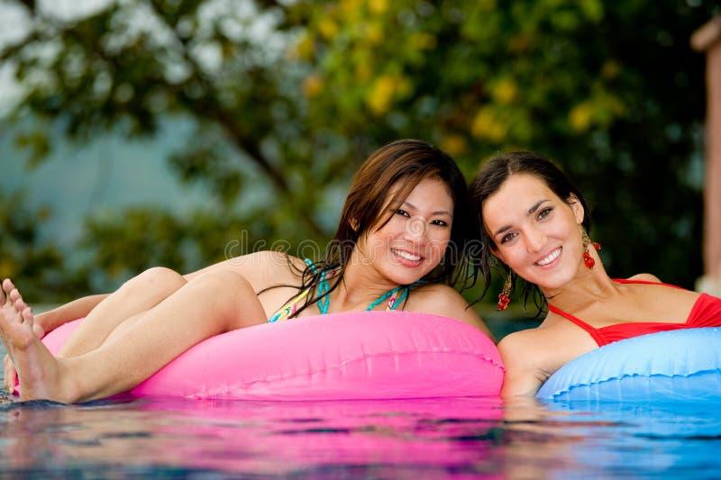 Muchachas en piscina foto de archivo
