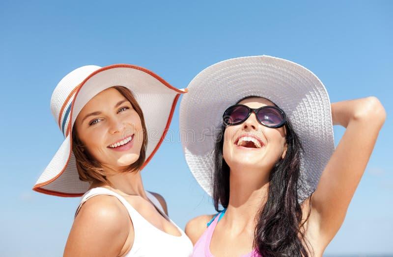 Muchachas en sombreros en la playa imagenes de archivo