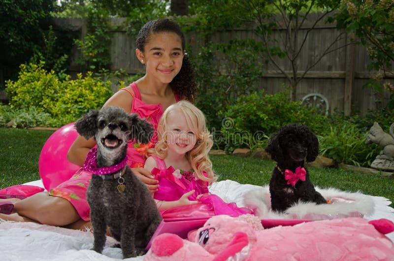 Muchachas en yarda con sus perros imagen de archivo