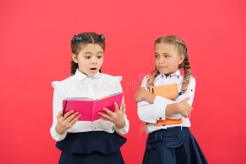 Muchachas famosas por la obsesi?n con efectos de escritorio Libro del control del uniforme escolar de los ni?os de las muchachas  fotos de archivo libres de regalías