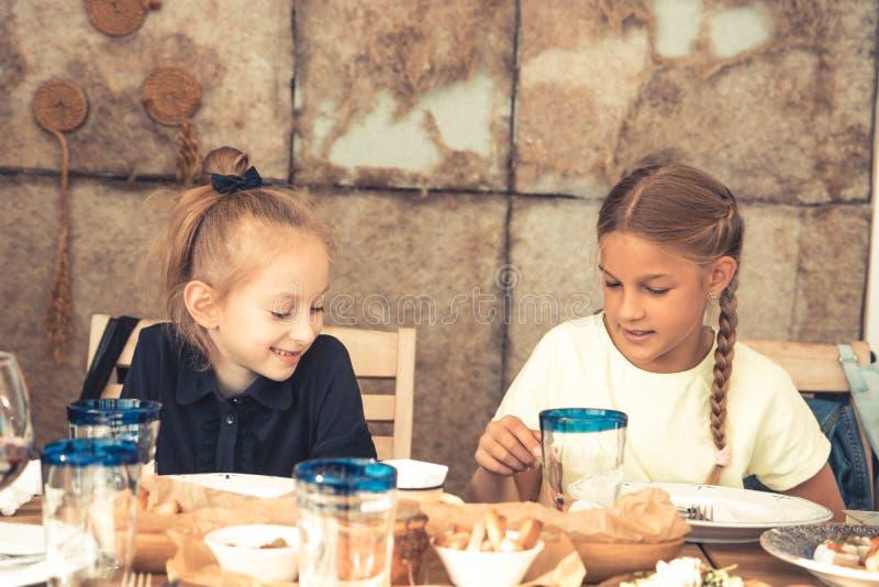 Muchachas felices de la hermana de los niños que tienen un rato de resto en el restaurante del café que habla junto forma de vida foto de archivo libre de regalías